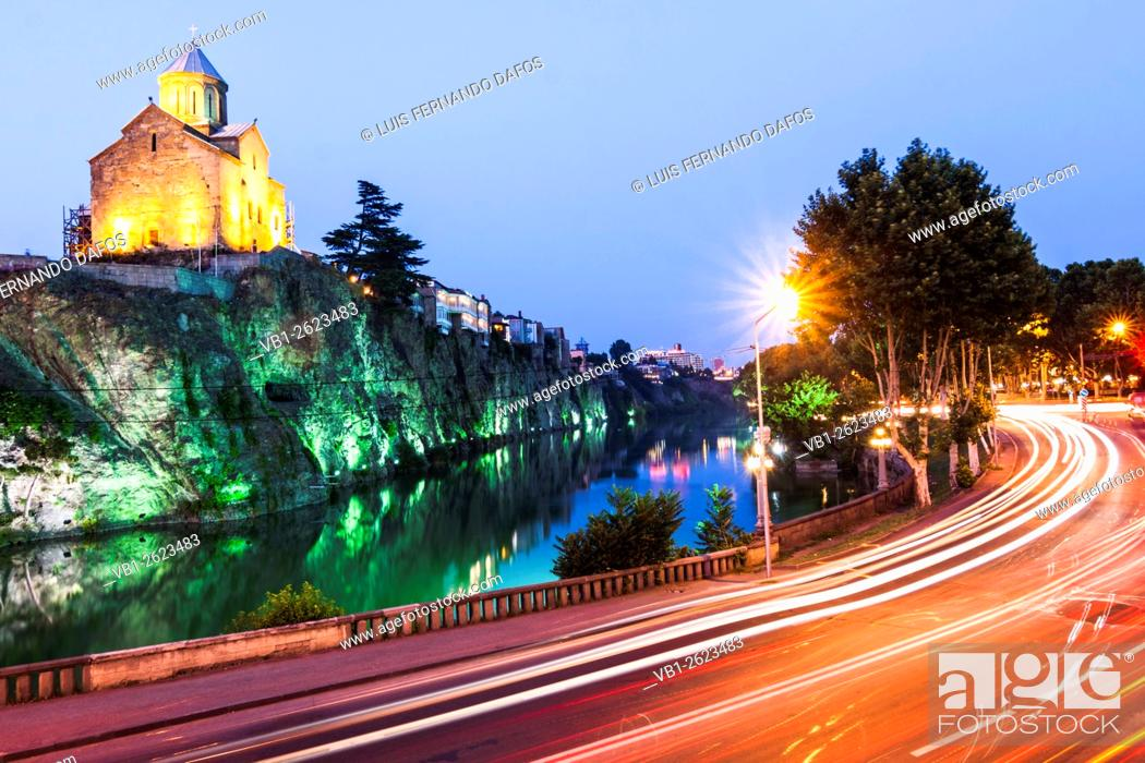 Imagen: Metekhi church and Avlabari quarter iluminated at dusk with traffic motion trails in foreground, Tbilisi, Georgia.