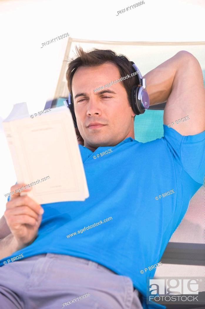 Stock Photo: Man reading a book on a lounge chair.