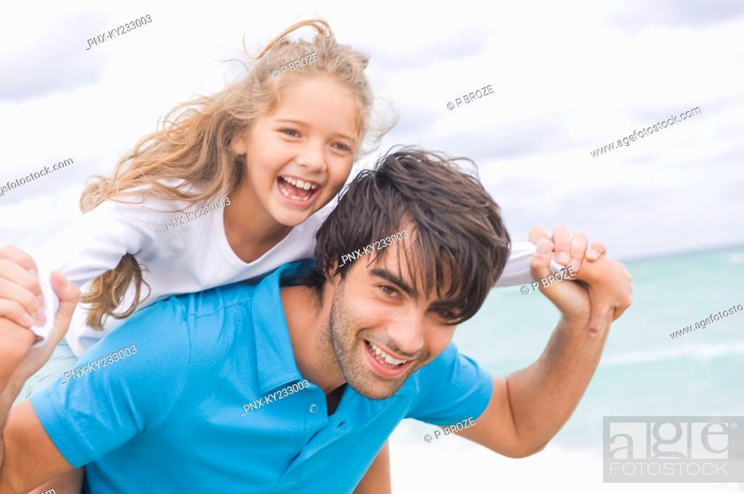 Stock Photo: Man giving his daughter piggyback on the beach.
