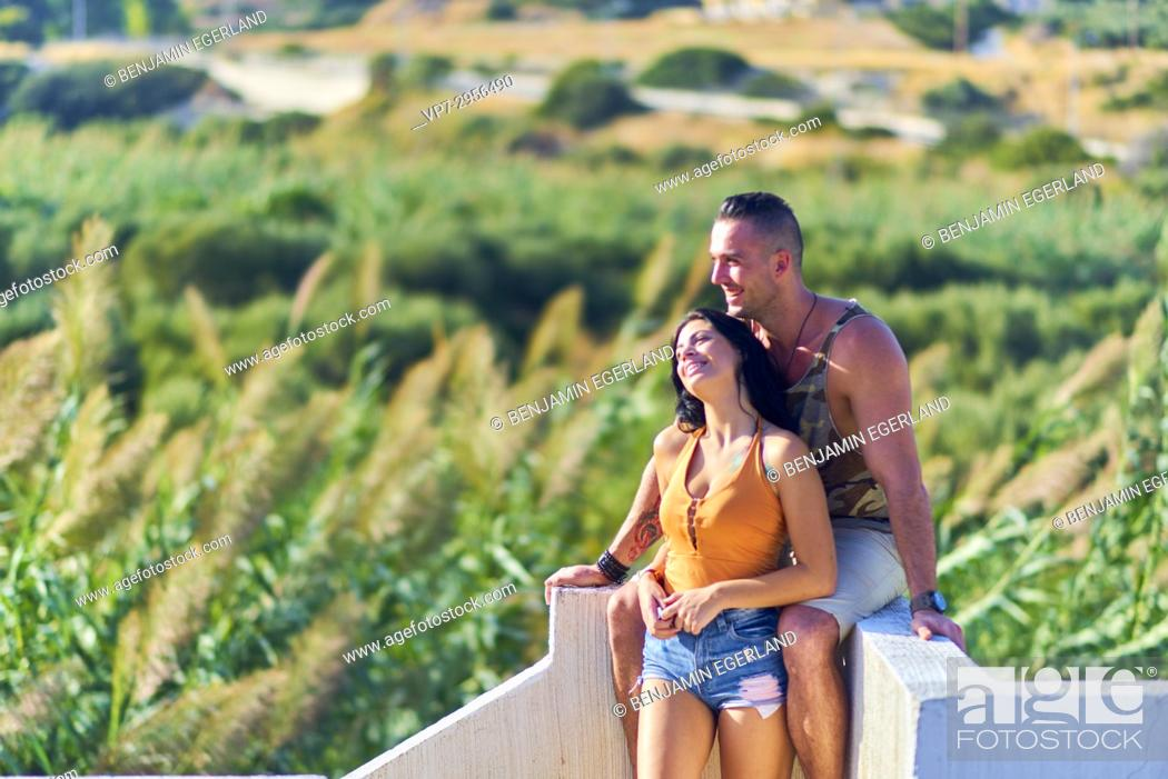Stock Photo: happy young couple leaning on wall in nature. Greek ethnicity. In holiday destination Hersonissos, Crete, Greece.