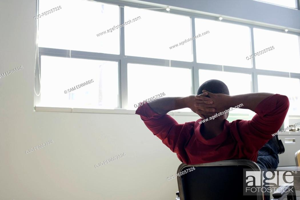 Stock Photo: Businessman at desk leaning back relaxing.