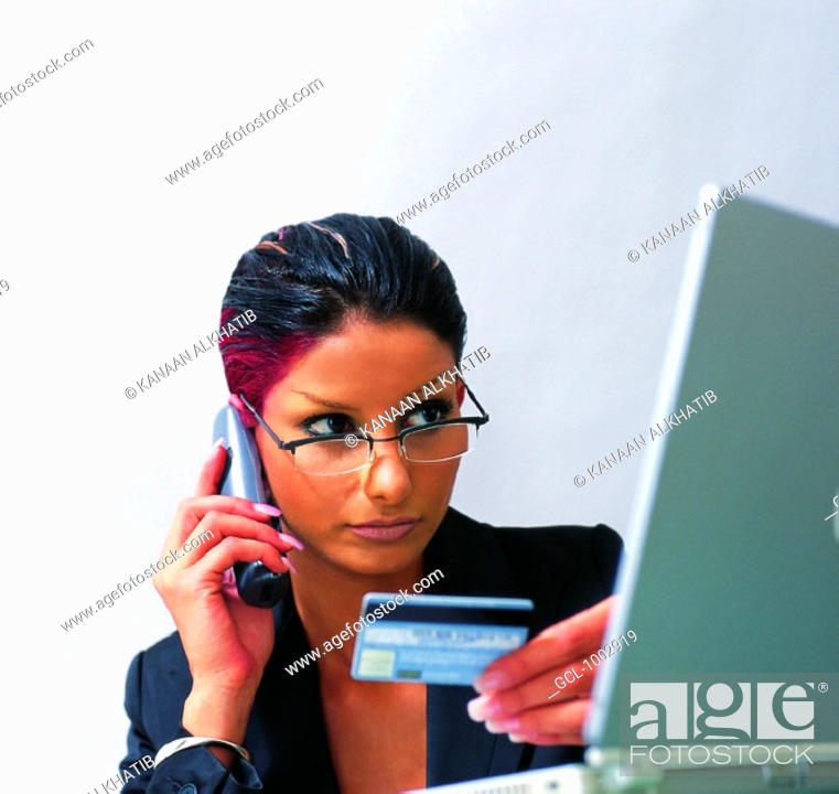 Stock Photo: Woman paying over the phone with credit card.