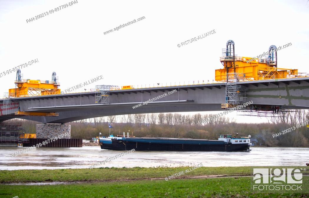 Stock Photo: 13 February 2020, Hessen, Wiesbaden: An inland waterway vessel passes under the freshly assembled bridge section. To complete the Schiersteiner Bridge (A 643).