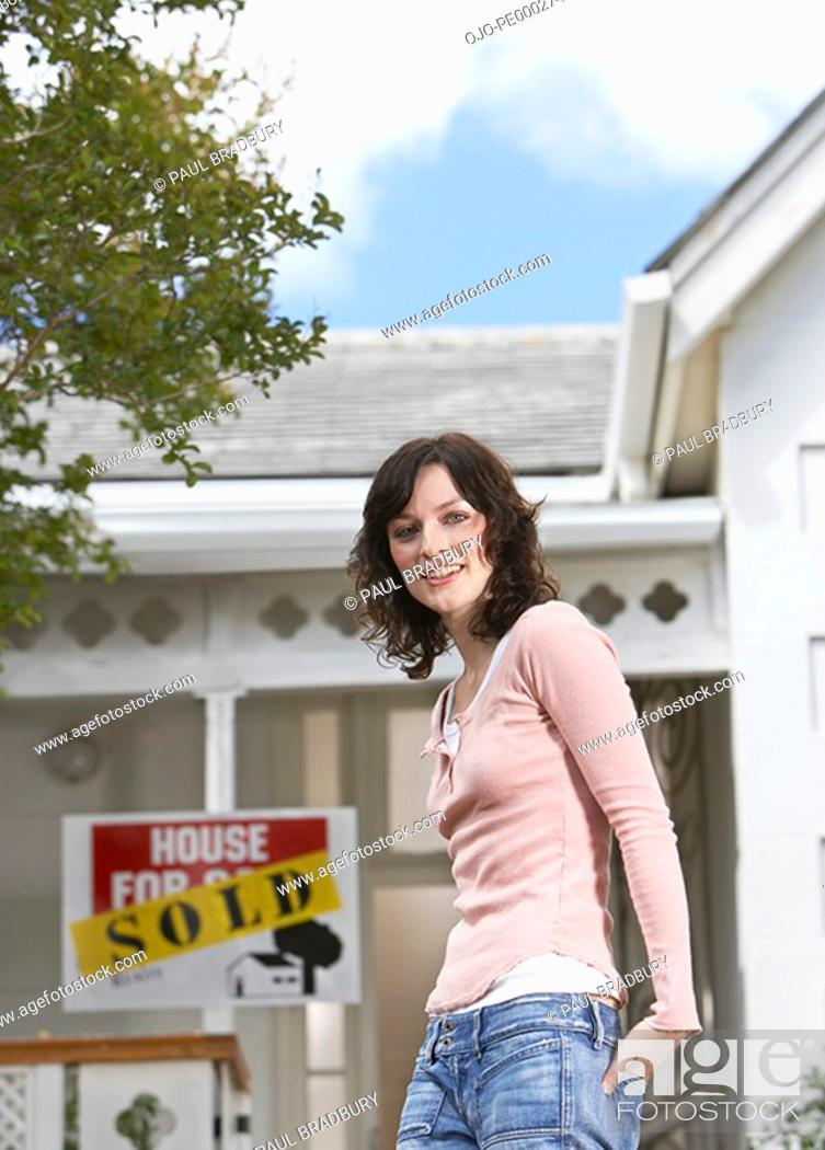 Stock Photo: Woman standing in front of house with sold sign.
