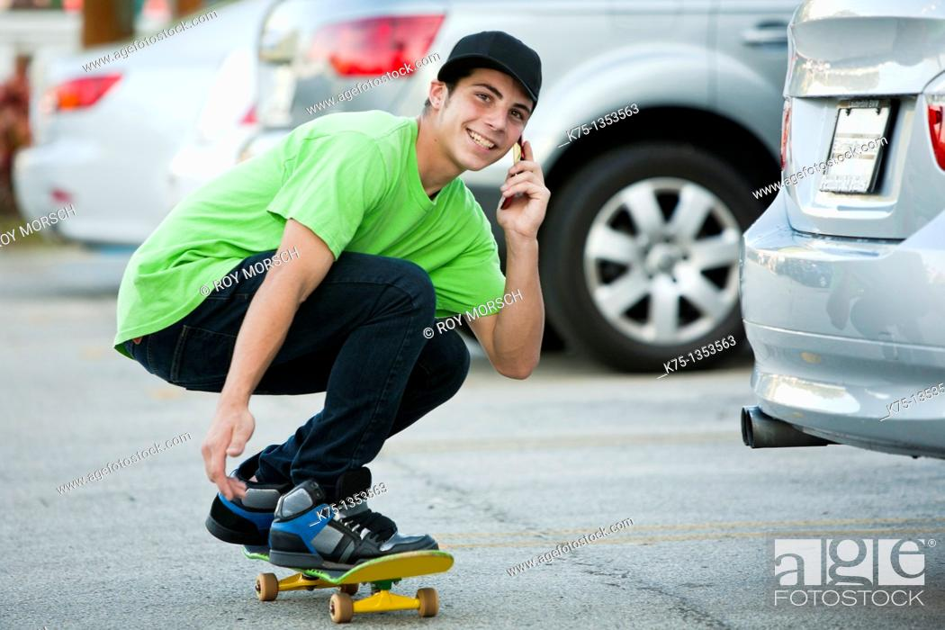 Stock Photo: teen on skateboard and cell phone.