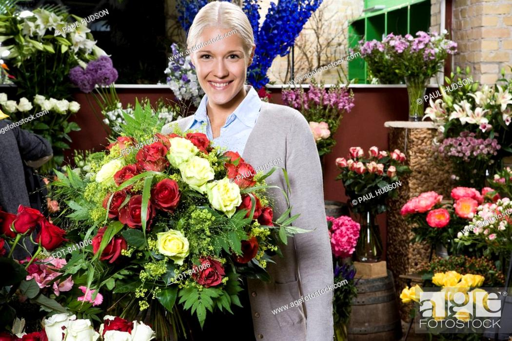 Stock Photo: A woman holding a bouquet of flowers in a florists.