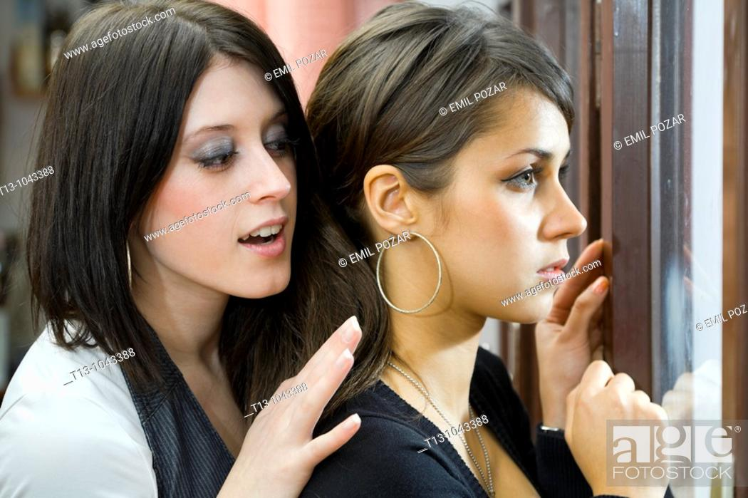 Stock Photo: Looking over her shoulder, two girlfriends behind a window.