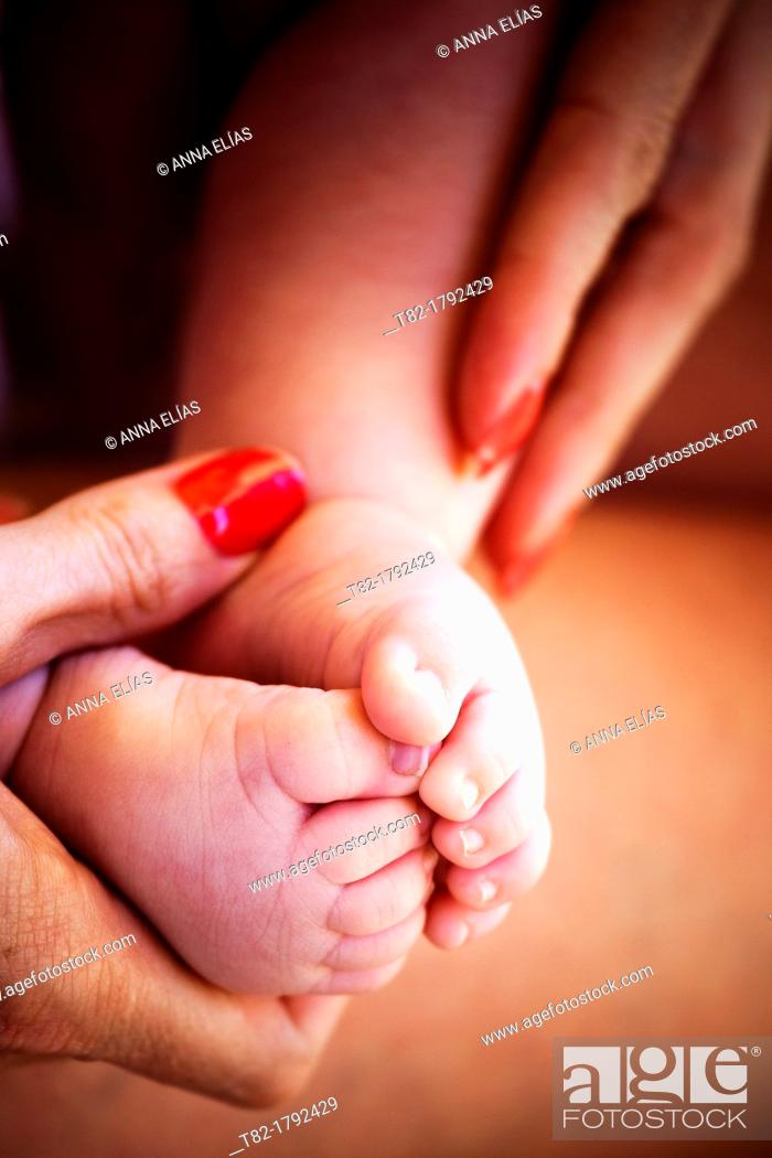 Stock Photo: close-up of baby feet on the hands of a woman.