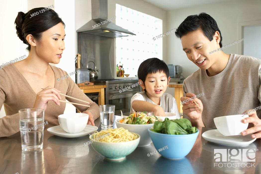 Stock Photo: Young parents watching son stick hand in bowl at kitchen table during meal.