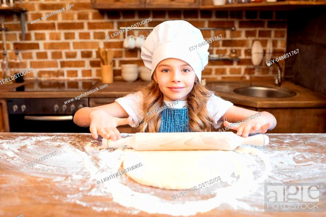 Stock Photo: girl in chef hat rolling out raw pizza dough.