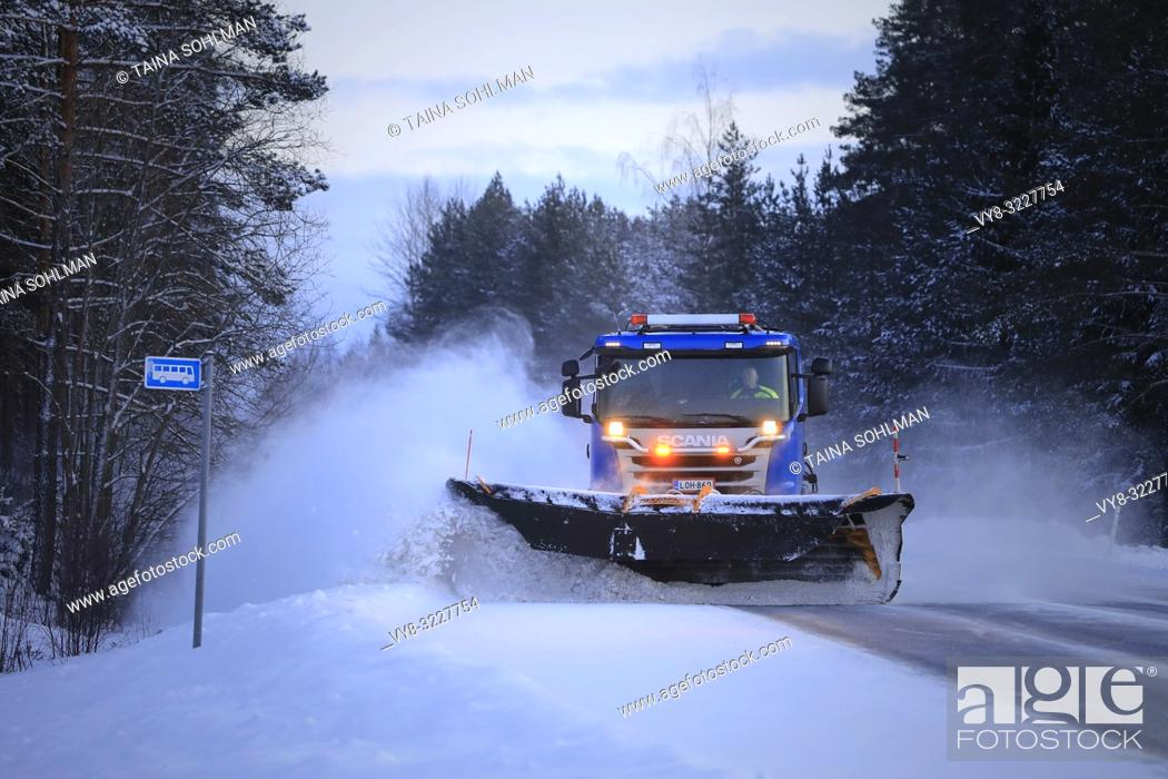 Stock Photo: Salo, Finland - January 18, 2019: Blue Scania truck equipped with snowplow clears a snowy bus stop by the highway in South of Finland at winter dusk.
