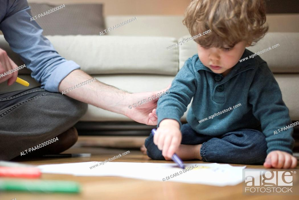 Stock Photo: Toddler boy sitting on floor with father, drawing on paper.