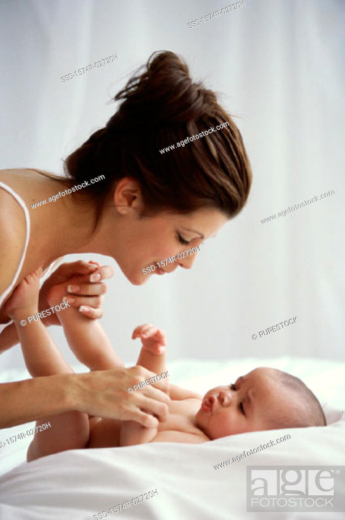 Stock Photo: Side profile of a mother playing with her baby boy.