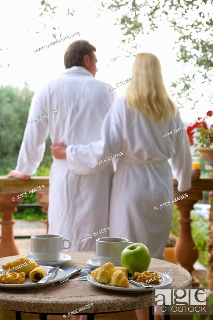 Stock Photo: Couple in bathrobes eating breakfast on patio.