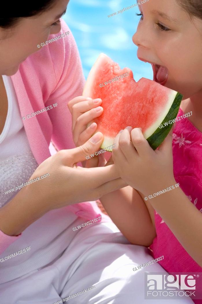 Stock Photo: Close-up of a girl eating a slice of watermelon.