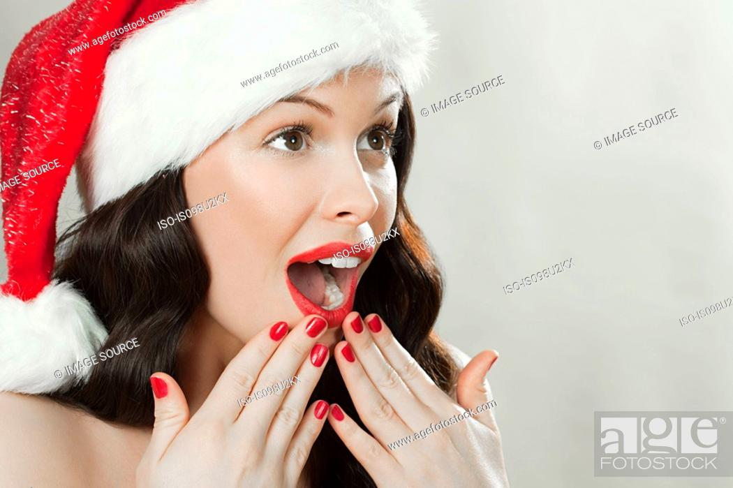 Stock Photo: Young brunette woman wearing Santa hat.