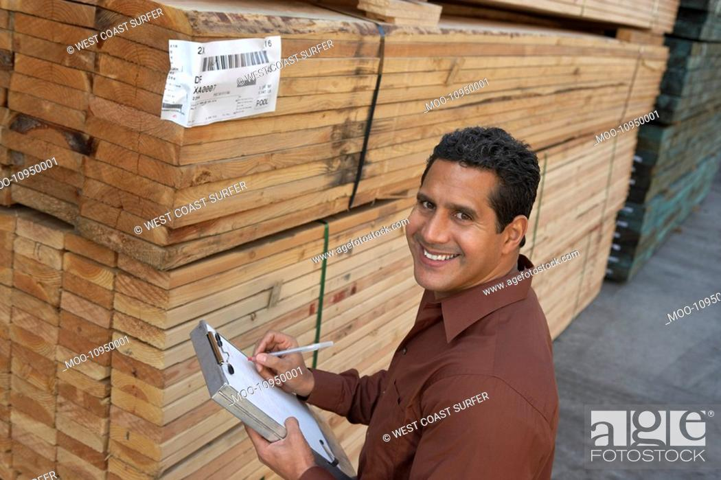 Stock Photo: Worker taking notes on clipboard by stack of wood in warehouse elevated view.