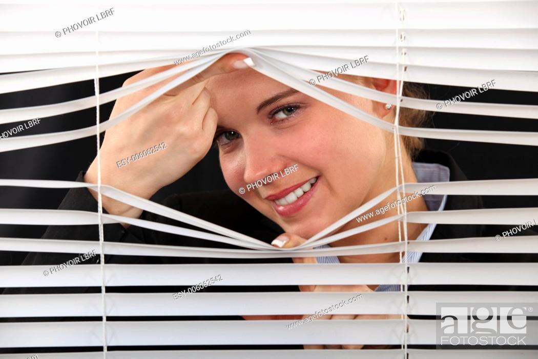 Stock Photo: woman looking through the blinds.