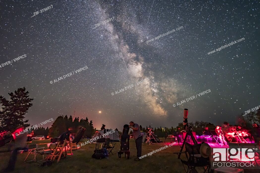 Stock Photo: An observer gazes skyward with his Dobsonian reflector telescope at the Saskatchewan Summer Star Party on August 9, 2018.