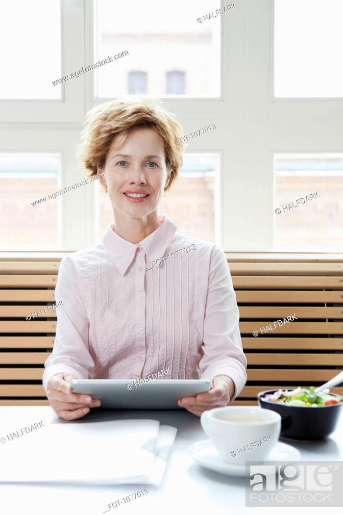 Stock Photo: A businesswoman using a digital tablet on his lunch break.
