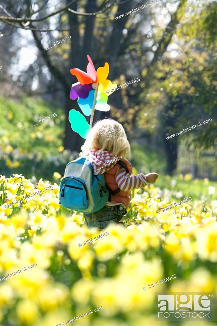 Stock Photo: Girl with pinwheel walking through daffodil field.