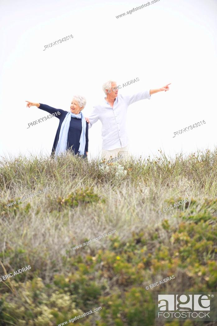 Stock Photo: Senior couple pointing at different direction against clear sky.