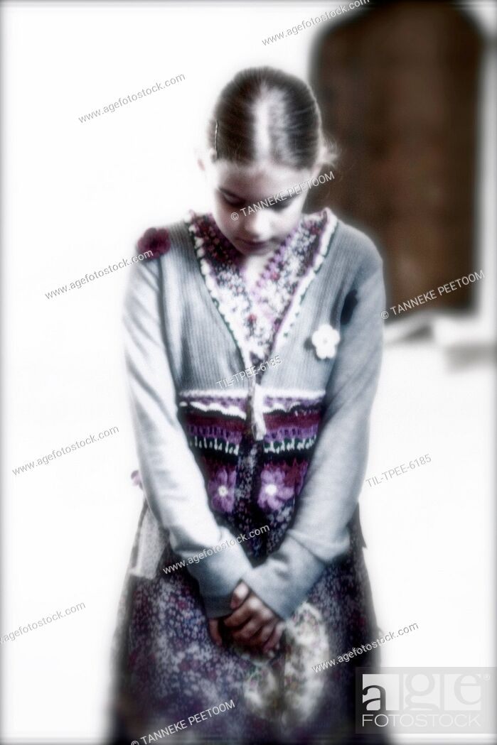 Imagen: Young girl standing alone looking down.