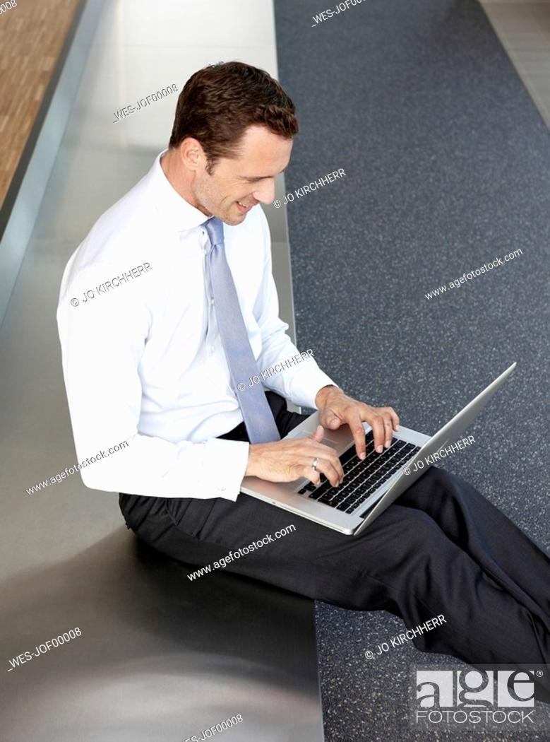 Stock Photo: Germany, Cologne, Businessman sitting on bench in corridor using laptop, portrait.
