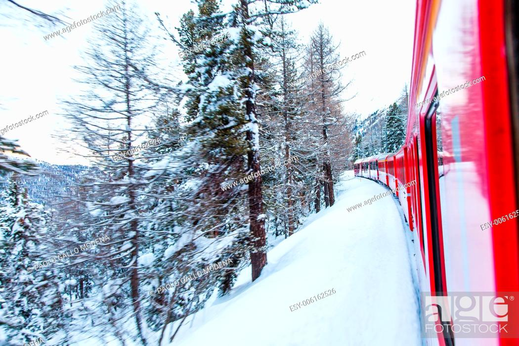 Stock Photo: The famous Bernina red train, Unesco monument, in the middle of a winter storm.