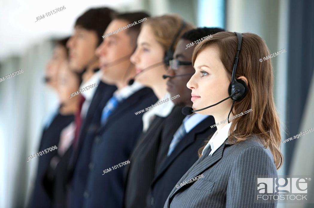 Stock Photo: Business people standing in a row with headsets and looking away.