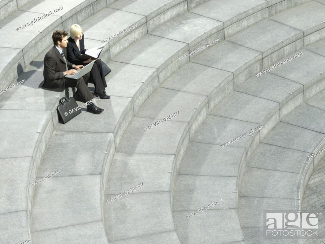 Stock Photo: Business man and woman sitting on spiral stairs using laptop elevated view.