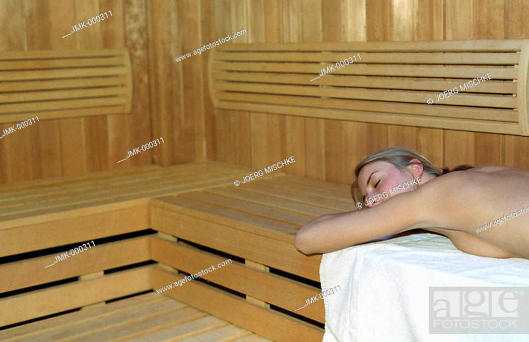 Stock Photo: young woman lying on a wooden bench in a sauna cabin.