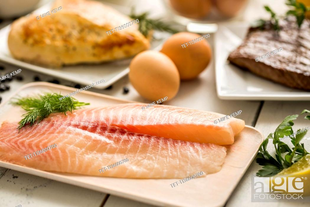 Photo de stock: Raw tilapia fish on plate, chicken and eggs in background.