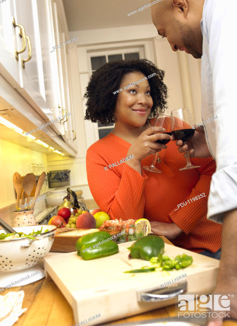 Stock Photo: Couple Making a Toast of Red Wine Cooking by Their Kitchen Counter.