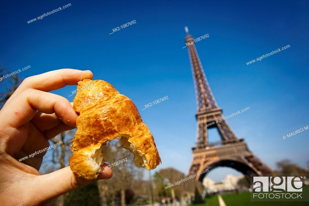 Stock Photo: hand holding a croissant in Eiffel Tower, Paris.