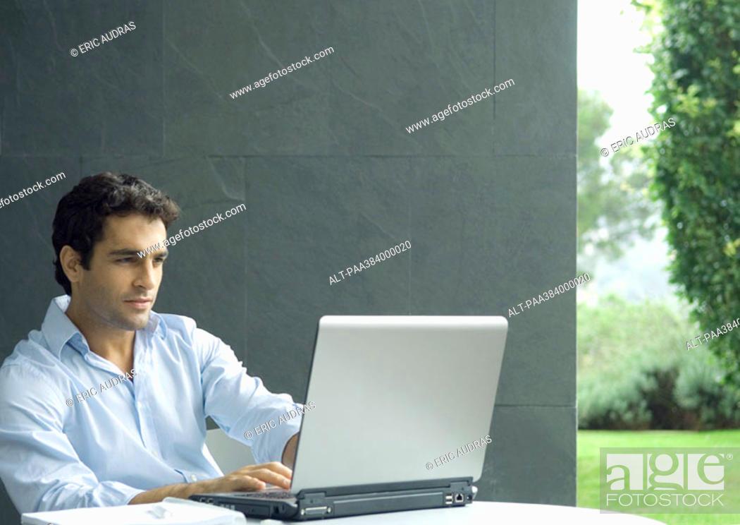 Stock Photo: Man using laptop outdoors.