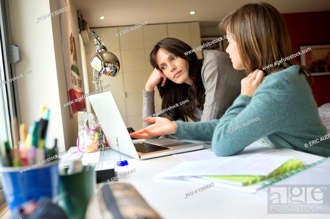 Stock Photo: Girl studying with her mother on a laptop at home.