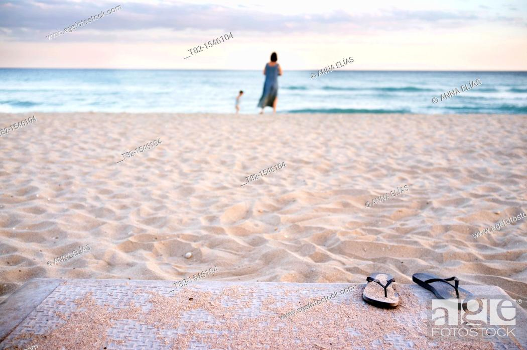 Stock Photo: Beach slippers on sand at fore and woman and child on the beach in background, Calafell, Tarragona, Spain.