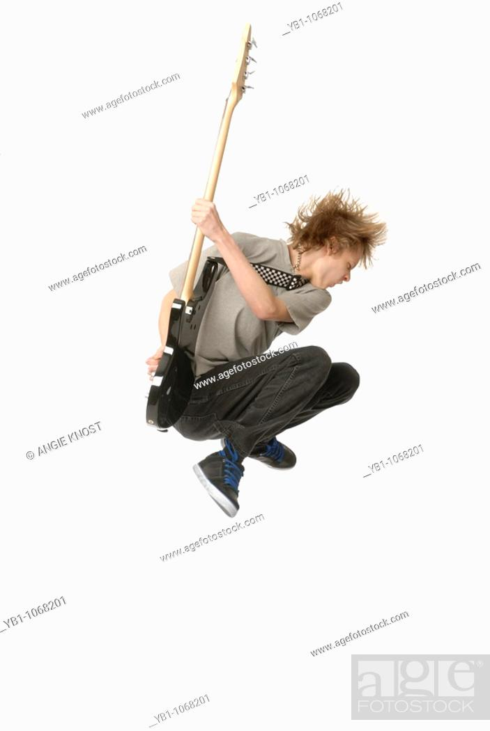 Stock Photo: Teenage boy jumping in the air while playing bass guitar.