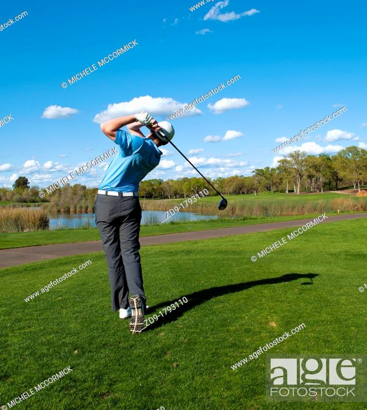 Stock Photo: A golfer hits his drive off the first tee at Granite Bay Golf Club.