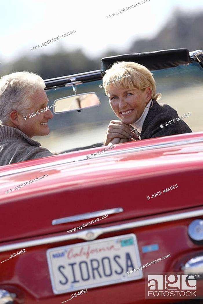 Stock Photo: Senior couple driving along country road in red convertible car, smiling, rear view, portrait.