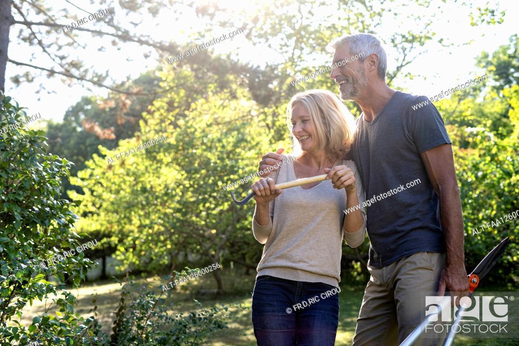 Photo de stock: Cheerful mature couple with gardening equipment standing in backyard.