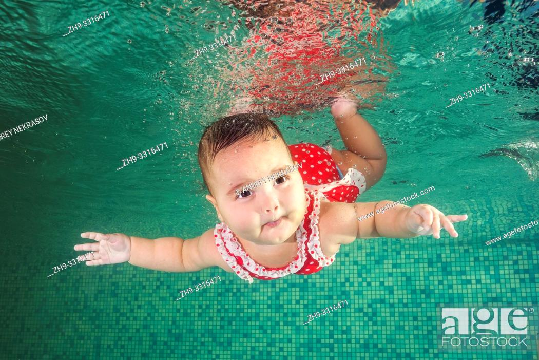 Stock Photo: A little girl in red swimmiing suit learns to swim underwater in the pool. Baby swimming underwater in the pool. Healthy family lifestyle and children water.