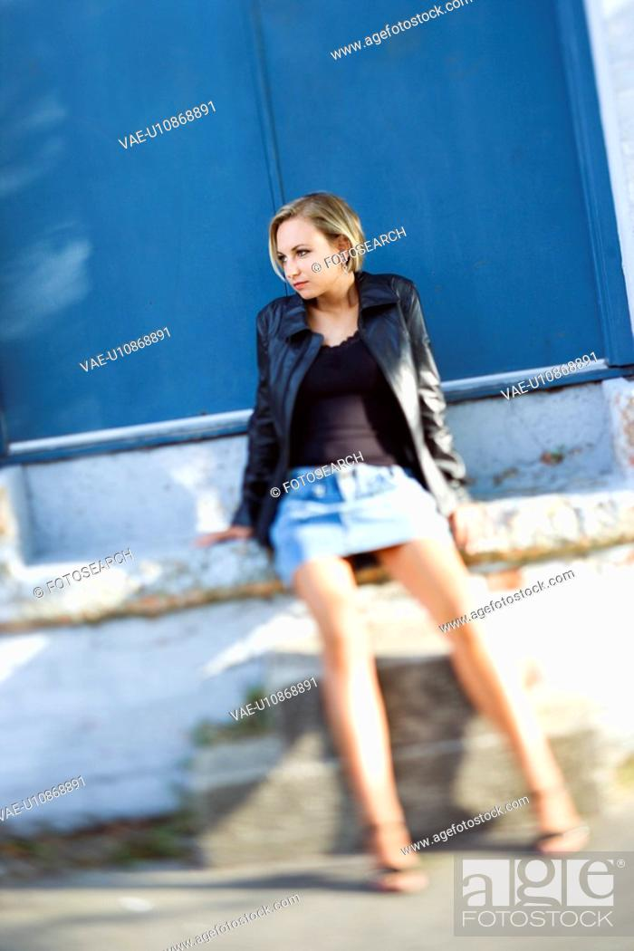 Stock Photo: Caucasian mid-adult blonde woman wearing blue jean mini skirt leaning against building.