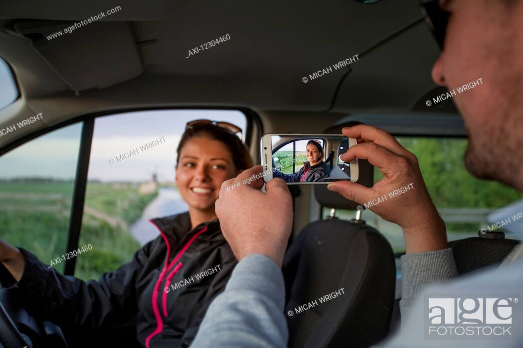 Imagen: A man takes a photograph of a young woman with a smart phone while sitting in a vehicle; Egmond aan Zee, Holland.