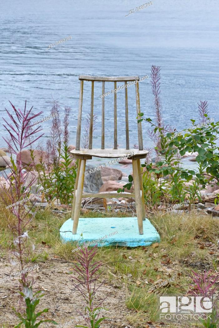 Stock Photo: A wooden chair is standing on a piece of turquoise styrofoam on a grassy beach, facing away from the sea. Baltic Sea, Västernorrland, Sweden, Europe.
