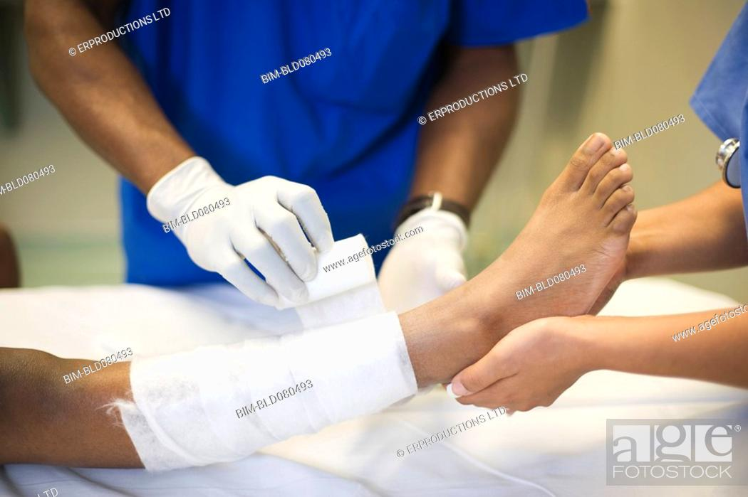 Stock Photo: Doctors treating girl's leg with bandages.