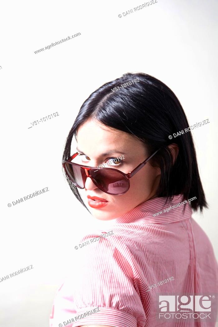 Stock Photo: Portrait of a brunette woman with sunglasses in a studio shot.