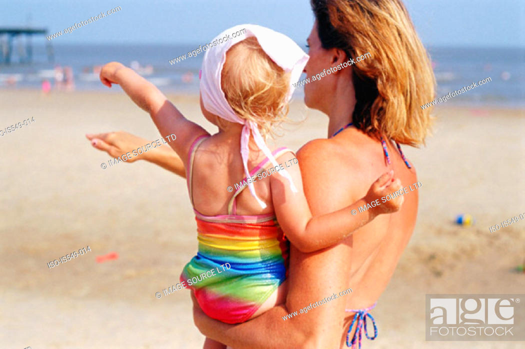 Stock Photo: Woman carrying a toddler on the beach.