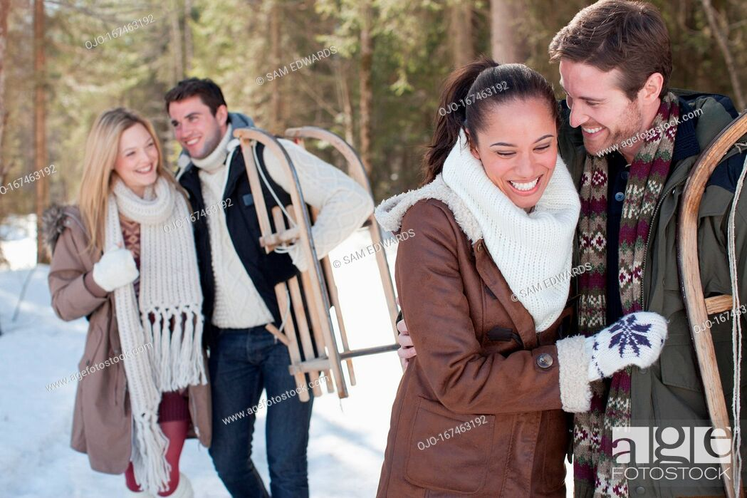 Stock Photo: Portrait of smiling couple with sled in snowy woods.